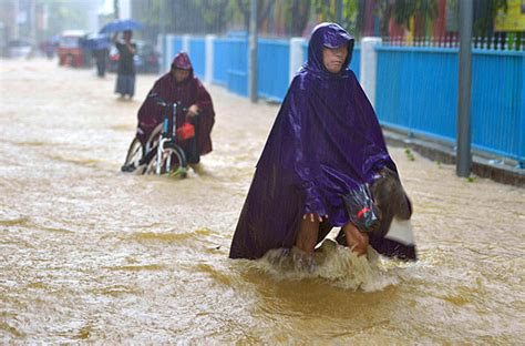 Residents navigate a flooded street in Lingao, Hainan